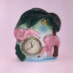 This is a nice pair of pink Flamingos standing below a palm tree. This clock is marked 1986 on the base. The clock is not working. This item is