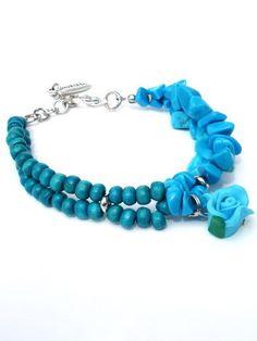 Deze armband van Per Elle is gemaakt van turquoise halfedelstenen en houten kralen. De armband heeft een turquoise roos als bedel.