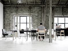 Guy working in open office with exposed brick walls | Murray Mitchell