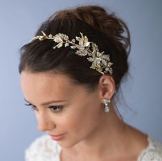 LANA FLORAL GOLD HEADBAND   Wedding headpiece offers a whimsical touch of nature to complement your bridal hairstyle. This headpiece features rhinestone encrusted and frosted leaves accented with rhinestones and Swarovski crystals for a delicate botanical design. Branches adorned with dusty golden accents are speckled throughout. Rhinestones run the length of the headband for added sparkle. Pin loops are located on both ends and can be easily fastened in your hair with bobby pins…