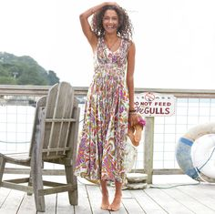 """Enchanting day or evening, our tropical print cotton sundress tempts and teases with a plaited """"apron"""" cascading from the shirred, elasticized bodice. Dry clean. Imported. Sizes 2 to 16. Approx. 53-1/4""""L."""