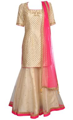 This set features an ivory shirt in silk base with all over light gold sequins and pearlhand embroidered small botis on the front of the shirt with a sheer key hole back with matching dori tie up with gold kundan and pearl embroidered tassel hangings. It features a beautiful gold dabka, zari, cutdana, sequins, stone and pearl intricatehand embroidery around the neckline. It is paired with a matching sharara in net base with an underlayer of satin and features all over light gold sequins…