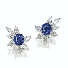 Pair of sapphire and diamond cluster earclips.  Set with 2 cushion-shaped sapphires together weighing 15.88 carats, surrounded by 12 pear-shaped diamonds weighing a total of 12.70 carats, and 4 marquise-shaped diamonds weighing 4.28 carats, mounted in platinum.