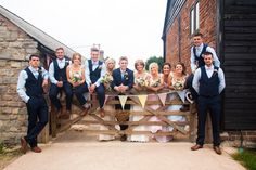Bridal party portrait on a rustic fence - Image by Julie Warner Photography - Wendy Makin Lace Wedding Dress & flower crown for a rustic wedding in a barn with pastel DIY decor, mis-match bridesmaids gowns and groomsmen in bow ties.
