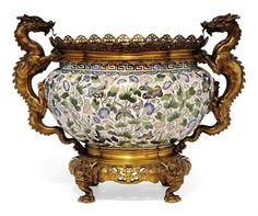 A CHINESE CLOISONNÉ ENAMEL MOUNTED JARDINIÈRE   THE CLOISONNÉ, 19TH CENTURY   Decorated with butterflies amongst morning glory sprays and foliage, the later mounts with dragon design