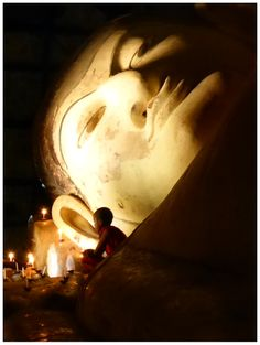 Young Buddhist monk to-be at the reclining Buddha of one of the temples of Bagan, Myanmar.