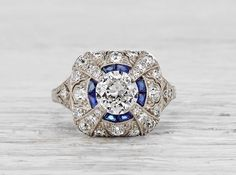 Antique Edwardian ring made in platinum and centered with an approximately .85 carat EGL certified old European cut diamond with E-F color and SI2 clarity. Accented with single cut diamonds and sapphires. Circa 1915.