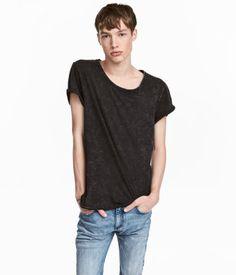 Negro. Camiseta maxilavada en punto flameado de algodón. Modelo con escote holgado sin rematar, costura central en la espalda, dobladillos cosidos en las