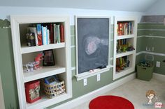 Built in bookshelves flank a built-in chalkboard in this child s playroom.