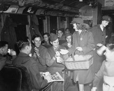 """A Red Cross """"Donut Dolly"""" serves her sugary fare to American GIs on a train returning from German POW camps that were liberated by the Russians. April 9, 1945"""