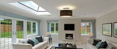 This living room has an asymmetrical ceiling, with a skylight on only one side of the room. The modern color scheme coordinates with the peaceful warmth of the skylight. Living Room Ceiling, Interior Design, Home, Living Room Flooring, Flat Roof Skylights, Room Lights, Modern Color Schemes, Ceiling Lights Living Room, Skylight Living Room