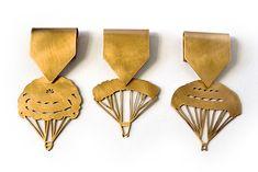 """Marie Pendariès. Brooch: Parachutes Dorés, 2012. Golden copper. 9,5 x 4,5 cm. Durante la crisis financiera de 1929 los directores de los bancos arruinados se suicidaban tirándose por las ventanas de sus sedes. Hoy en día, los ex-directores se tiran con un """"paracaídas dorado"""" de varios millones de euros, aunque hayan dejado sin blanca a su empresa y sus empleados.  . Me parecía que esta élite tenía que ser condecorada con una medalla al mérito, reflejo de su éxito como ventajistas sin…"""