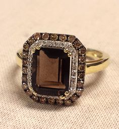 Smoky quartz surrounded by white diamonds and brown diamonds, set in yellow gold. Stunning.
