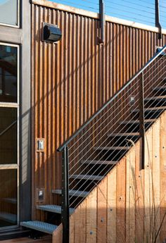 Portage Bay staircase in seattle by Dyna Contracting featuring metal and wood railing with corrugated metal siding