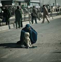 A beggar and her child at their regular 'pitch' on a speed bump in Kabul City.  They are there every day, despite the winter temperature never getting much above 0 degrees celsius.