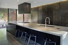 Gray Modern Kitchen With White Waterfall Countertop For a client who owns a company that manufacturers steel scales, Hufft Projects designed cabinetry that would reflect his business and his life. The gunmetal cabinets are made from galvanized hot-rolled steel with a clear-coat finish over an MDF substrate. They have integrated edge pulls to maintain a clean, seamless appearance.