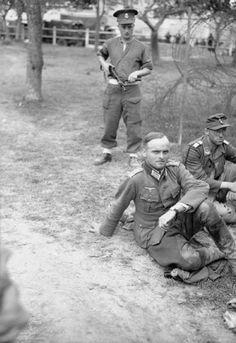 German prisoners taken during Operation 'Goodwood' under guard, 19 July 1944.