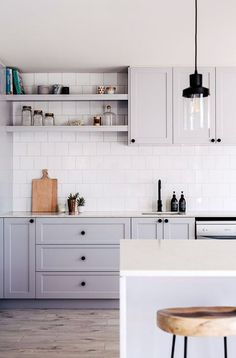 gray kitchen cabinets with white tile backsplash and black pendant lights. / sfgirlbybay
