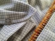 Grey and white small checked wool with carnelian colored beads at the ends, and RSM's sterling silver logo. $250