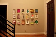 Kids artwork hung on clipboards.  Great idea.