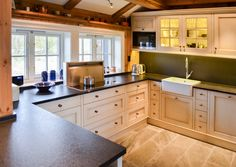 Hand painted kitchen in solid pine from Os Trekultur. The kitchen is tailored to the room after the customer's wishes. Worktop in black granite. Smart downdraft ventilation that works well in front of windows. Large white porcelain sink fits well with cottage-style.