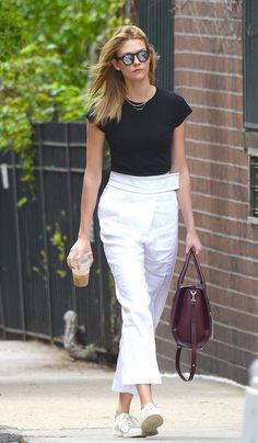 Karlie Kloss dresses down a sharp pair of trousers by pairing them with a black tee and white sneakers