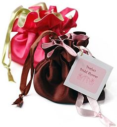 "Satin Chic Jewelry Pull String Pouch Size: 4""W x 4""H Give your bridal party these lovely Satin Jewelry Pouches filled with their own special attendant jewelry to show them just how much they mean to you. Our beautifully crafted satin pouches come in your choice of mocha brown with a soft pink interior or hot pink lined with lime green. The pouches are reversible so that they will complement nearly any color scheme. Each pouch stays snugly closed with satin drawstrings in accent…"