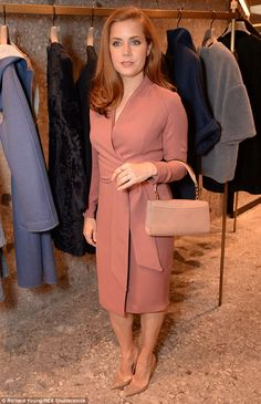 Looking good: Amy, 40, looked typically stylish in a salmon pink dress with a wrap detail that exuded vintage glamour as she posed for photos shortly after arriving at the one-off event