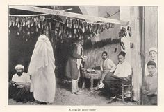 Turkish men and children and one veiled woman gathered about a boot shop. 1900