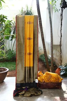 ALLURING MUSTARD YELLOW BENARES COTTON EMBLAZONED WITH PINK, BLACK AND GOLD BHUTTAS. THE INTRICATELY WOVEN GOLD-BLACK BORDER AND PALLU GIVES THE SAREE A FABULOUS FINISH