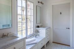Well appointed bathroom boasts polished nickel framed mirror mounted on a shiplap trim beneath dark nickel picture lights illuminating white single washstands accented with polished nickel pulls and honed carrera marble countertops fitted with sinks paired with polished nickel faucets.