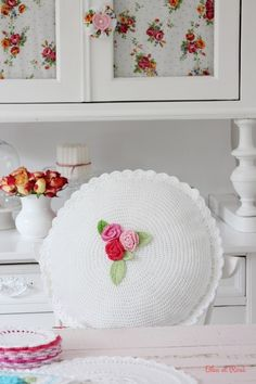 White crocheted pillow with pretty flowers in center.