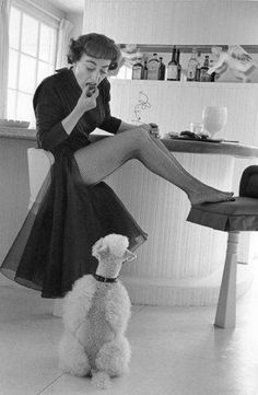 Joan Crawford playing with her dog.