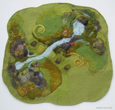 "This play mat, about 18""x18"", has silk ""water"" applied onto the base, it is both glued and needle felted along the edges. The rocks and moss give it a three dimensional quality."