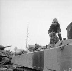 A little Dutch boy helps to refuel a Sherman tank near Sittard, 20 December 1944.