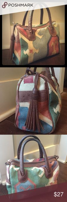 Vintage hand woven tribal purse w/ leather tassel Beautiful Vintage hand woven tribal purse w/ leather handles and tassel. In great shape. With leather tassel attached to upper zipper. Interior is black and clean with one zipper pouch. Bags