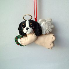 This Pup sculpture is a sweet little angel Christmas Ornament. Holding a wreath for the holiday. Hand sculpted polymer clay dog. Made with love and care!  Item Measures a little under 3 inches wide Thanks for looking!  ***This item can be made in other breeds/animals/colors/styles/or similar again, just convo me :)  I will make your dog as a Christmas Angel if you ask! Using your photos...Makes a great gift too
