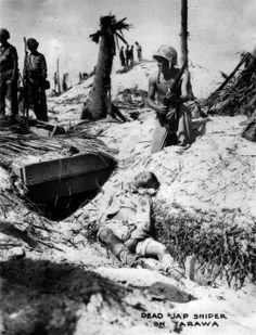 A Marine posing with the body of a dead Japanese sniper. Tarawa.