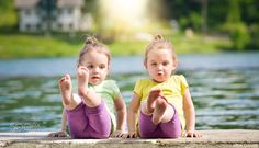 Twin girls exercising on a lake shore by gasparij