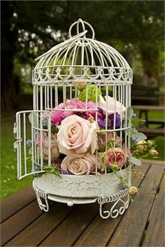 Bird cages filled with flowers make for a beautiful table centrepiece