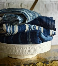 Denim-colored textiles with striped patterns in ceramic serving bowl