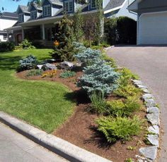 landscaping ideas with rocks corner fence | Stone border along driveway surrounding flower bed.