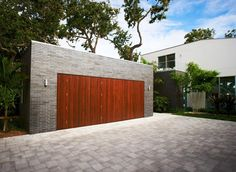 18 Inspirational Examples Of Modern Garage Doors // The rich colored wood of these garage doors, stands out and contrasts the brick.