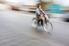 Cyclist in traffic on the city roadway - Cyclist in blurred motion against a background of an urban landscape