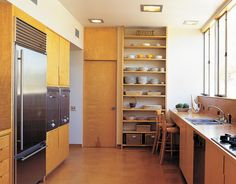 Simple floor-to-ceiling shelves provide easy access to dishes, place mats, and other kitchen necessities. Loose items are kept in wicker baskets, which add texture and visual interest while keeping order.