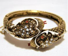 Mid Century signed Art figural snake bangle bracelet Antiqued gold tone, with red rhinestone eyes, white enamel highlights, and small white glass cabochons, red enamel tong... #gotvintage #reptile