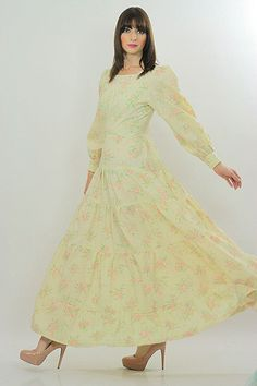 Vintage Boho Bridal Dress Cream in color with pink floral print Fashioned of polyester Has tiers of ruffles on the skirt Dress zips up the back Condition Excellent vintage condition. Measurements Garm