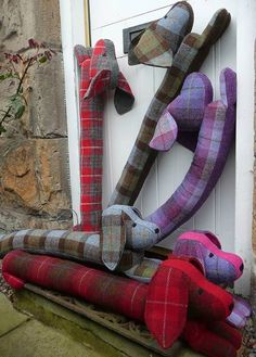 multicoloured collection of dashund shaped, Harris tweed  draught excluders handmade in Harris tweed by Queenie on Notonthehighstreet