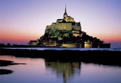 Mont St. Michel France.  Located on France's northwest coast, Mont St. Michel appears to rise from the surrounding tide flats. First used as a military stronghold, it was later home to a monastery in the 8th century. The Romanesque abbey at the top of the island, built in the 11th century, eventually became an important destination for Catholic pilgrims. Connected to the mainland by a causeway, Mont St. Michel is surrounded by dangerous quicksand and rapidly rising tides.