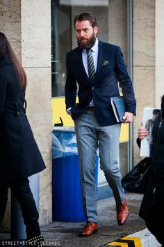 Shop this look on Lookastic: https://lookastic.com/men/looks/blazer-dress-shirt-dress-pants-oxford-shoes-tie-pocket-square-belt/8642 — Light Blue Dress Shirt — Green Print Pocket Square — Navy Vertical Striped Tie — Navy Blazer — Tobacco Leather Belt — Grey Wool Dress Pants — Tobacco Leather Oxford Shoes